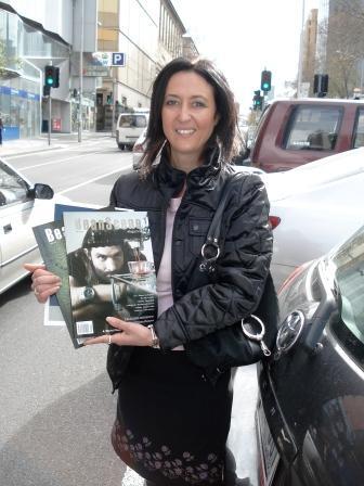 Maria, holding Bean Scene magazine which she writes for